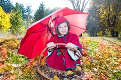 Cute child girl playing with umbrella in leaves in autumn Stock Photo