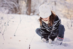 Cute child girl plays with snow in winter forest Royalty Free Stock Images