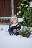 Cute child girl plays in winter snowy garden. Cute child girl in owl hat plays in winter snowy garden with basket of fir branches Stock Photo