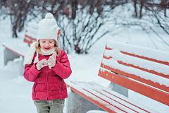 Cute child girl portrait in winter park with wooden bench Royalty Free Stock Photos