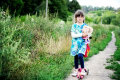 Cute child girl poses outdoors with baby doll Royalty Free Stock Images