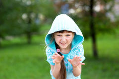 Cute child girl poses outdoors with scary face. Cute child girl in blue hood poses outdoors making scary face stock images