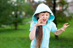 Cute child girl poses outdoors with scary face Royalty Free Stock Image
