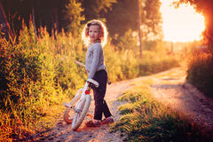 Cute child girl riding bicycle on summer sunset country road Royalty Free Stock Images