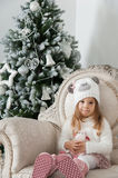 Cute child girl with sheep toy and Christmas tree Stock Image