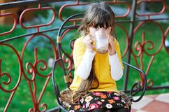 Cute child girl sitting with a cup of tea outdoors royalty free stock photos