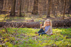 Cute child girl sitting in green leaves in early spring forest. Cute child girl sitting in green leaves in early spring sunny forest Royalty Free Stock Photography