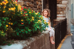 Cute child girl sitting on stone wall and smells flowers. Traveling in Europe on summer vacation Stock Photo