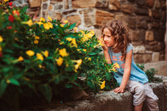 Cute child girl sitting on stone wall and smells flowers. Traveling in Europe on summer vacation Royalty Free Stock Images