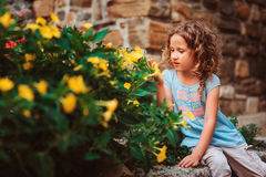 Cute child girl sitting on stone wall and smells flowers Stock Images