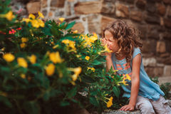Cute child girl sitting on stone wall and smells flowers. Traveling in Europe on summer vacation Stock Images