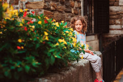 Cute child girl sitting on stone wall and smells flowers. Traveling in Europe on summer vacation Royalty Free Stock Photo