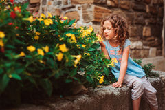 Cute child girl sitting on stone wall and smells flowers. Traveling in Europe on summer vacation Stock Photography