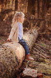Cute child girl sitting on the tree in early spring forest. And looking out of camera Royalty Free Stock Images