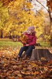 Cute child girl sitting on wooden log with autumn leaves bouquet Royalty Free Stock Photos