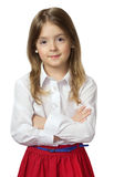 Cute child girl standing in white shirt & red skirt isolated on Royalty Free Stock Photos