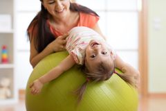 Cute child girl stretching on pilates fitness ball with mom in gym stock photos