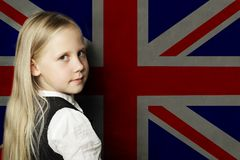 Cute child girl student against the UK flag background. English language school concept stock photos
