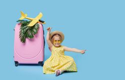 Cute child girl in summer dress with a pink suitcase and toys airplane is dreams of traveling to tropical countries after quaranti