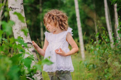 Cute child girl walking in summer forest with birch trees. Nature exploration with kids. Stock Photos