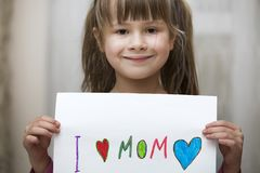 Cute child girl wit sheet of paper with colorful crayons painted words I love Mom. Art education, creativity concept stock photo