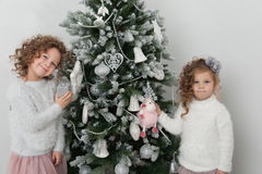 Cute child girls near Christmas tree Stock Photos