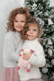 Cute child girls with sheep toy near Christmas tree Royalty Free Stock Images