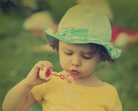 Cute child in hat blowing bubbles. Stock Photography