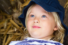Cute child in hat relaxing. Cute child in hat lying on some dried bamboo relaxing royalty free stock photos