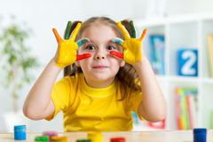 Cute child have fun painting her hands. Cute child girl have fun painting her hands Stock Image