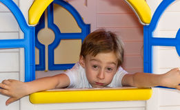 Cute child having a bored expression in toy house Royalty Free Stock Photography