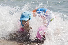 Cute child having some fun in ocean waves. Young happy girl swimming and having some fun in ocean Stock Photo