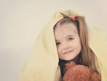 Cute Child Hiding Under Blanket. A little child is having fun under a blanket and hiding under the sheet with a teddy bear with copyspace for a message stock images