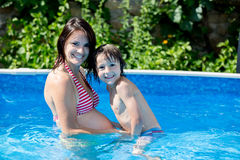 Cute child and his pregnant mom, swim in swimming pool Royalty Free Stock Image