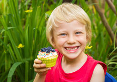 Cute child holding colorful homemade muffin in the garden. Cute child in garden holding colorful delicious homemade muffin covered in blueberries and sprinkles stock image