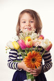 Cute child holding fresh spring flowers Stock Photos