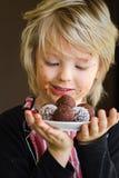 Cute child holding homemade chocolate treat. Cute child holding homemade chocolate bliss balls as a treat Stock Photo