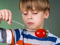 Cute child holding tomato on fork Stock Photos