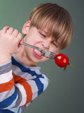 Cute child holding tomato on fork Royalty Free Stock Photos