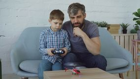 Cute child is holding transmitter and controlling flying helicopter while his father is trying to catch it with his