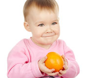 Cute child holds mandarin Royalty Free Stock Image