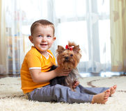 Cute child hugging dog indoor Stock Image