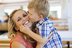 Cute child kissing mother. Beautiful mother and child being close to each other and being happy together Royalty Free Stock Image