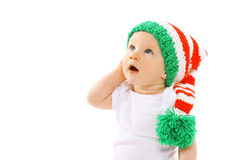 Cute child in knitted gnome hat surprised looking up on a white Stock Photos