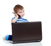 Cute child with laptop and mobile phone Stock Photography