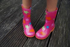 Cute child legs in rubber boots (galoshes) - shy Royalty Free Stock Image