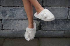 Cute child legs in slippers - cross legged Stock Photography