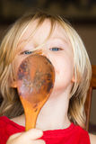 Cute child licking chocolate off a wooden spoon Stock Photography