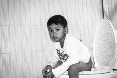 Cute child little asian boy defecate in toilet. Black and white tone stock photo