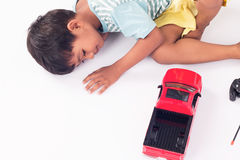 Cute child little boy lying play toy car royalty free stock photography